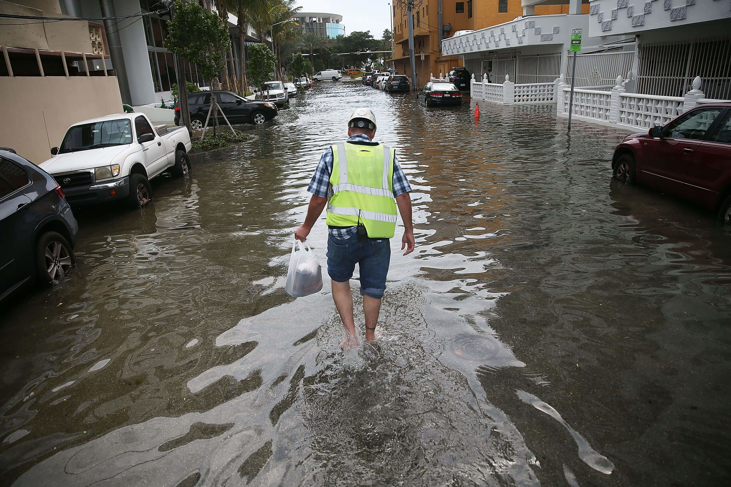 Howard Rogers walks through a flooded street during the King Tides of September 2015.